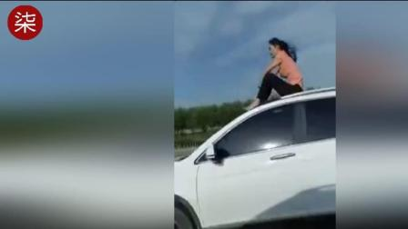 """实拍女子公路上坐车顶""""自由飞翔""""看呆众人 交警介入"""