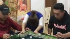 女子在旁边看别人打麻将,突然响起一首音乐,