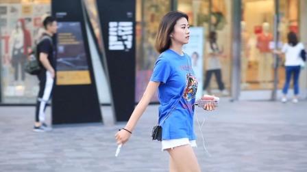 三里屯街拍:蓝T恤配白热裤,美女斜背包包秀身