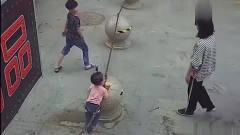一男一女两个小孩正在路边玩耍,女子从旁边经