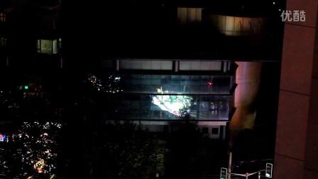 从十二楼窗口透过稀疏的秋叶看曝光过度的上海旅游节花车散场